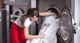 Worker removing linens from an industrial washing machine